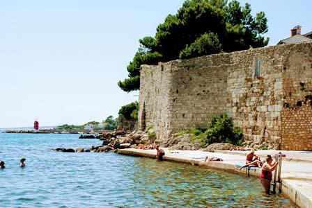 Bañito en piscinas naturales bajo las murallas romanas de Krk en Croacia