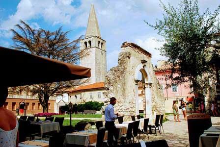 Restos romanos en la plaza Marafor y el campanario de la Basílica Eufrásica en Porec (Croacia)